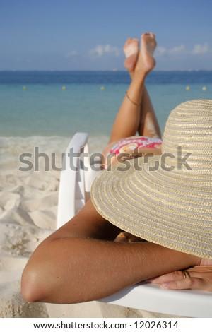 Woman sunbathing on a sun lounger on a tropical beach