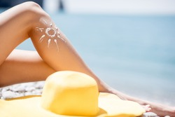 Woman sunbathing on the beach. Close-up view on the legs with lotion sun shape and yellow hat