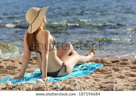 Woman sunbathing on the beach in summer with the sea in the background