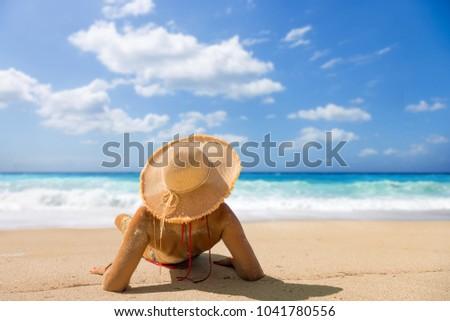 Woman suntanning at the beach #1041780556