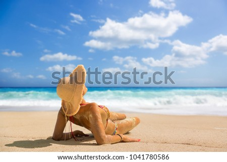 Woman suntanning at the beach #1041780586