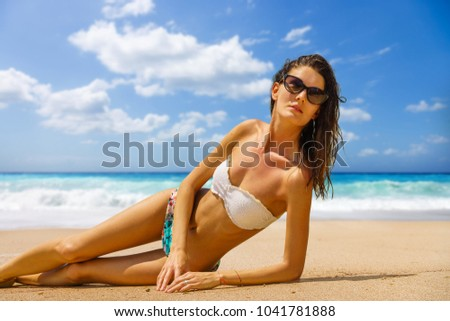 Woman suntanning at the beach #1041781888