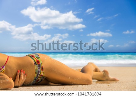 Woman suntanning at the beach  #1041781894