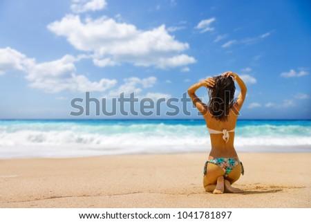 Woman suntanning at the beach #1041781897