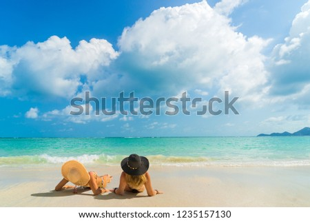 Woman suntanning - Winter holidays at the tropical beach #1235157130