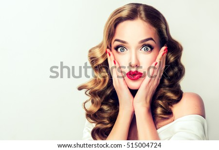 Woman surprise holds cheeks by hand .Beautiful girl  with curly hair  pointing to looking right . Presenting your product. Isolated on white background. Expressive facial expressions - Shutterstock ID 515004724