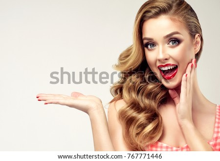 Woman surprise showing product .Beautiful girl  pointing to the side . Presenting your product. Expressive facial expressions emotions #767771446