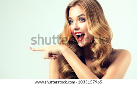 Woman surprise showing product .Beautiful girl  with curly hair  pointing to the side . Presenting your product. Isolated on white background. Expressive facial expressions #1033157965