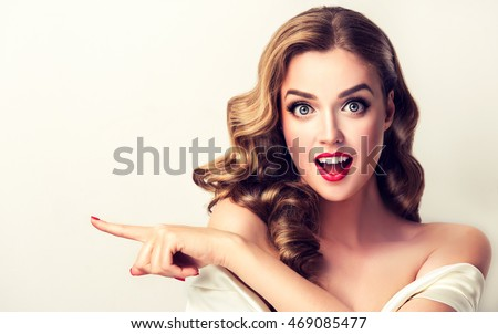 Shutterstock Woman surprise showing product .Beautiful girl  with curly hair  pointing to the side . Presenting your product. Isolated on white background. Expressive facial expressions