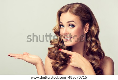Woman surprise showing product .Beautiful girl with curly hair pointing to the side . Presenting your product. Expressive facial expressions