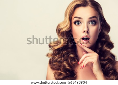 Woman surprise showing product .Beautiful  surprised ,  wonder  and shocked  girl  with curly hair  . Presenting your product. Expressive facial expressions