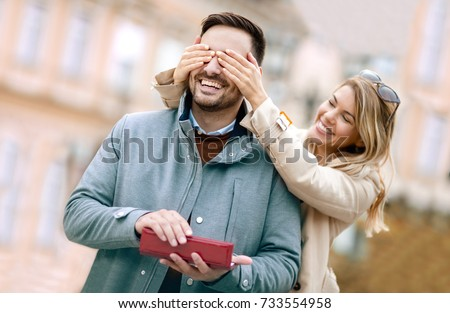 Shutterstock Woman surprising his boyfriend with a gift.Young woman with giftbox closing his boyfriend eyes to make a surprise for him.