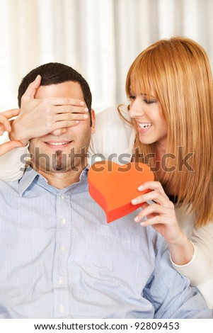 Woman surprising man with gift