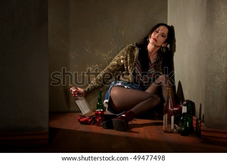 Woman surrounded by booze bottles in a hallway