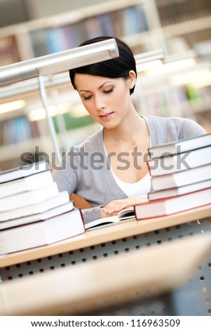 Woman surrounded with piles of books reads sitting at the desk at the library. Knowledge concept
