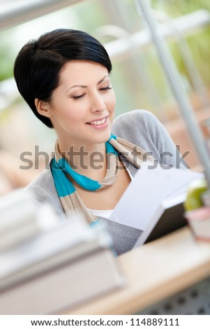 Woman surrounded with piles of books reads sitting at the desk at the reading hall. Training process