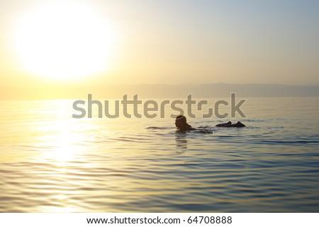 Woman swimming in a salt water of Dead sea.