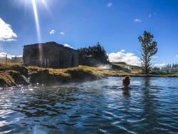 Woman swimming in natural thermal pool in fludir secret lagoon