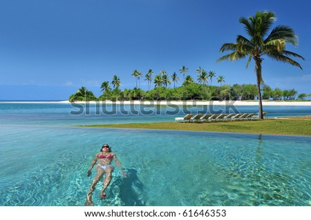 Woman swimming in the infinity pool under the sun in beautiful tropical beach resort in the Bahamas .