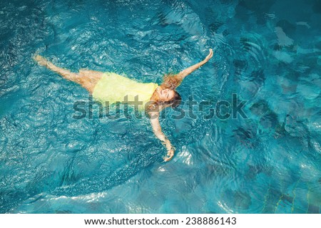 woman swimming in the pool - top view