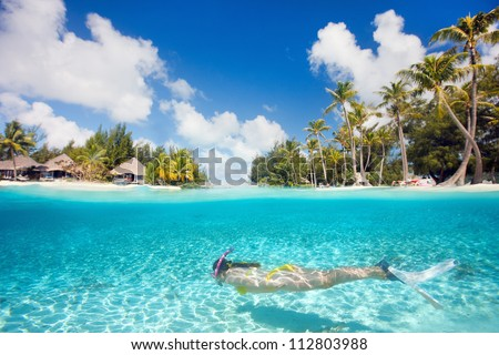 Woman swimming underwater in clear tropical waters in front of exotic island