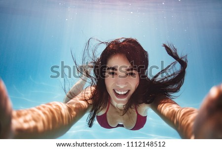 Woman swimming underwater in pool smiling and making a selfie. Young female swimmer shooting herself while swimming underwater.