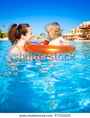 Woman swimming underwater in pool. Summer vacations