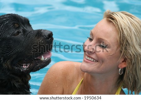 Woman swimming with rottweiler in pool