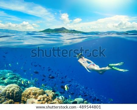Woman swims around a coral reef surrounded by a multitude of fish on the background Islands. North Sulawesi, Indonesia.