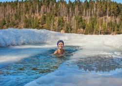 Woman swims in the ice hole on the background of the forest on sunny day