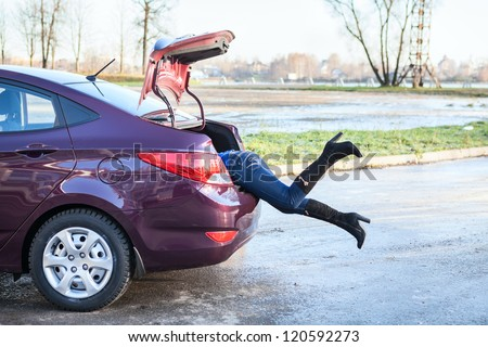 Woman swinging her legs into car luggage trunk