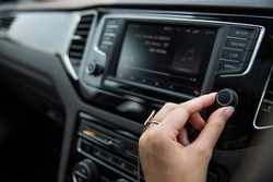 Woman switches the entertainment volume dial close-up. Close-up of the driver's arm includes the car interior parts.