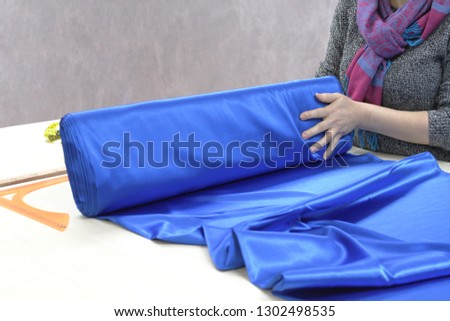 Woman tailor or seller of textiles unwinding a roll of fabric. Profession, atelier, textile shop #1302498535