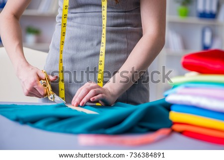 Woman tailor working on a clothing sewing stitching measuring fa #736384891