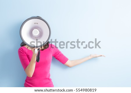 woman take microphone and show something to you isolated on blue background