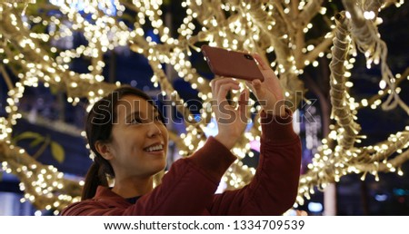 Woman take photo with cellphone of Christmas night #1334709539