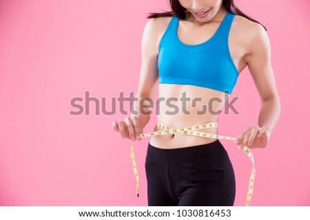 woman take waist scale on the pink background