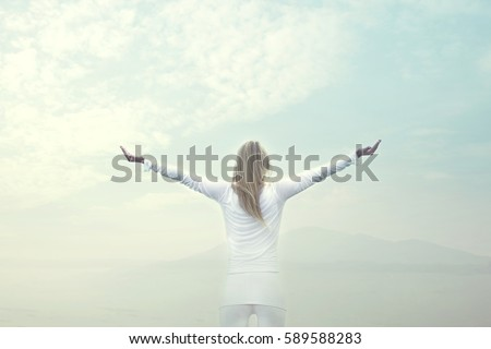 woman takes a breath in front of a blue sky
