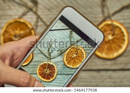 woman takes a photo of christmas decoration made of dried orange slices on her white modern smarthfone. Taking blogging conent for christmas and new year