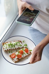 Woman takes a photo on smart phone, holding plate with rye crisp bread with creamy vegetarian cheese tofu, cherry tomato and rucola micro greens. Healthy food , tasty breakfast, gluten free, diet.