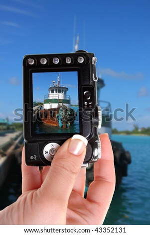 Woman takes a picture of a tugboat in the clear blue Caribbean ocean docked in the port of Nassau, Bahamas
