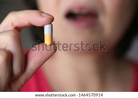 Woman takes a pill, girl putting capsule in open mouth. Sick female taking medicines, painkiller, antibiotic or vitamin