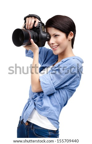 Woman takes images holding photographic camera, isolated on a white