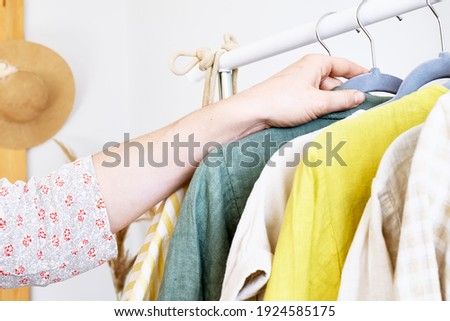 Woman takes linen dress on hanger from clothes rack. Slow Fashion. Conscious consumption. Crisis in the fashion industry, retail. Eco-friendly, Sustainable seasonal Sale concept. Zero waste. Сток-фото ©