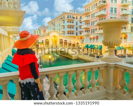 Woman takes photo with smartphone of Venice, Venetian style waterfront village at twilight. Tourism in Middle East. Photographer takes pictures at Qanat Quartier in Pearl-Qatar, Persian Gulf.