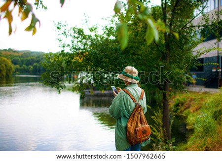 Woman takes pictures of autumn park. tourist holding phone mobile taking photo outdoor, lifestyle nature.