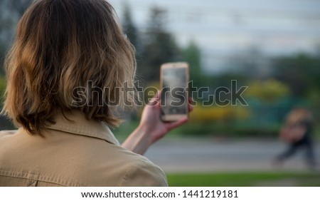 Woman takes pictures with her smart phone. View from the back. Follow someone and take photos.