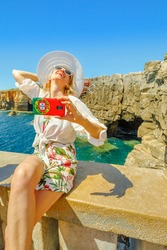 Woman takes selfie at Boca do Inferno in Cascais, Atlantic Ocean, Portugal.Female tourist takes pictures by mobile phone with Portugal flag of Hell's Mouth a touristic sightseeing spot. vertical shot.