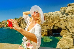 Woman takes selfie with Boca do Inferno cliff formation, Cascais, Atlantic Ocean, Portugal. Girl takes pictures by mobile phone with Portugal flag cover at Hell's Mouth touristic sightseeing point