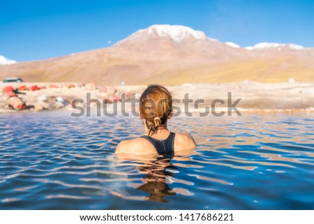 Woman taking a bath at El Tatio Geysers hot springs at Atacama desert, amazing thermal spring waters at 4500 masl inside Andes mountains scenic a place with an awe geothermal activity below the ground #1417686221
